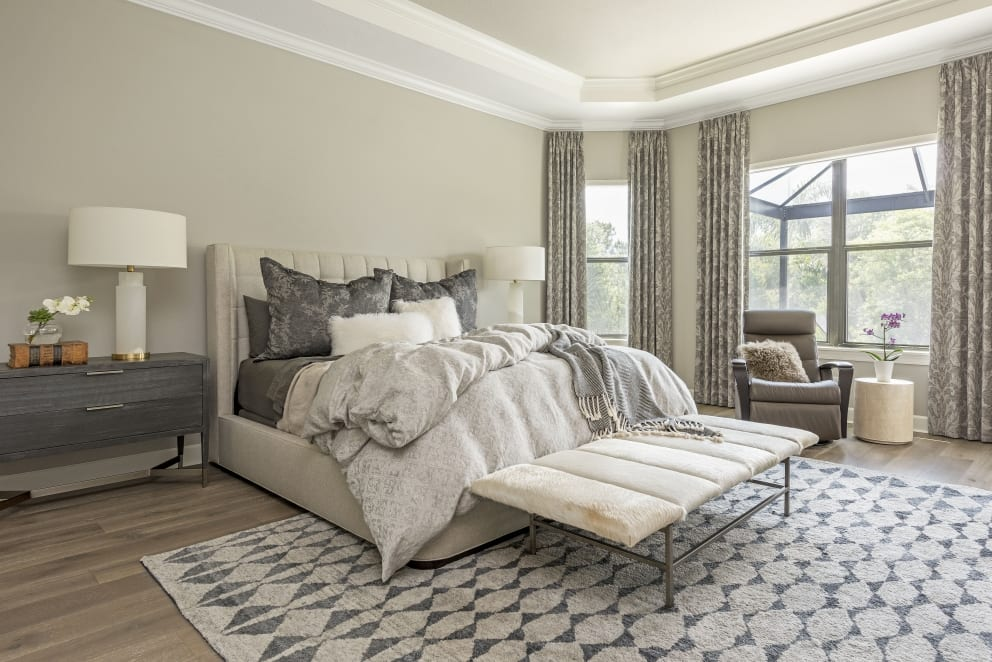 Bedroom Gray Cream Ruffled Duvet White Fur Pillows Gold Trim Bed Side Lamps Dark Wood Bedside Draw Animal Skin Bench