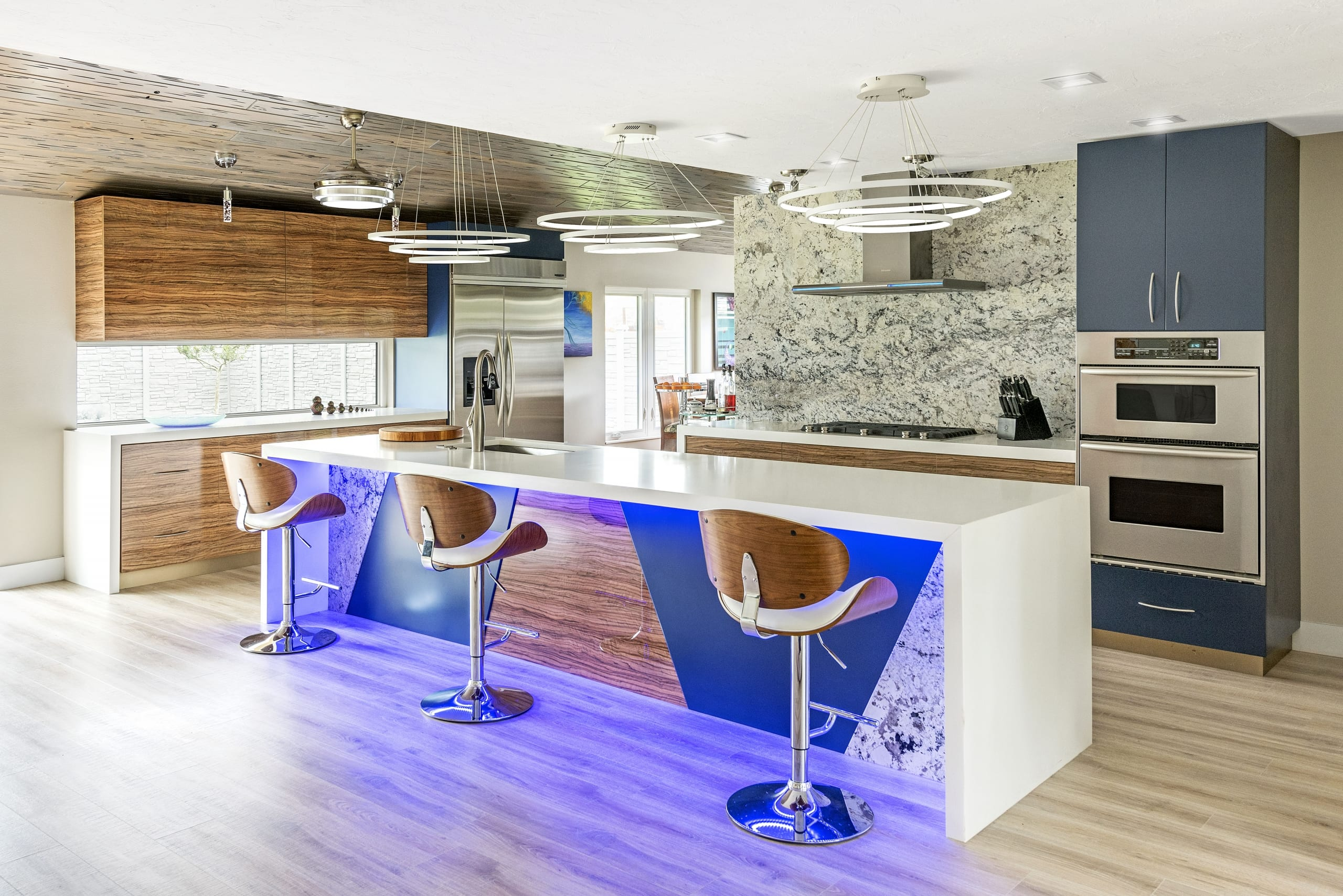 Kitchen Varnished Wood Cabinets Marble Splashback Gas Cooker Blue Cabinet White Top Breakfast Bar Island Neon Lights Blue Ceiling Lights Wood Slat Ceiling