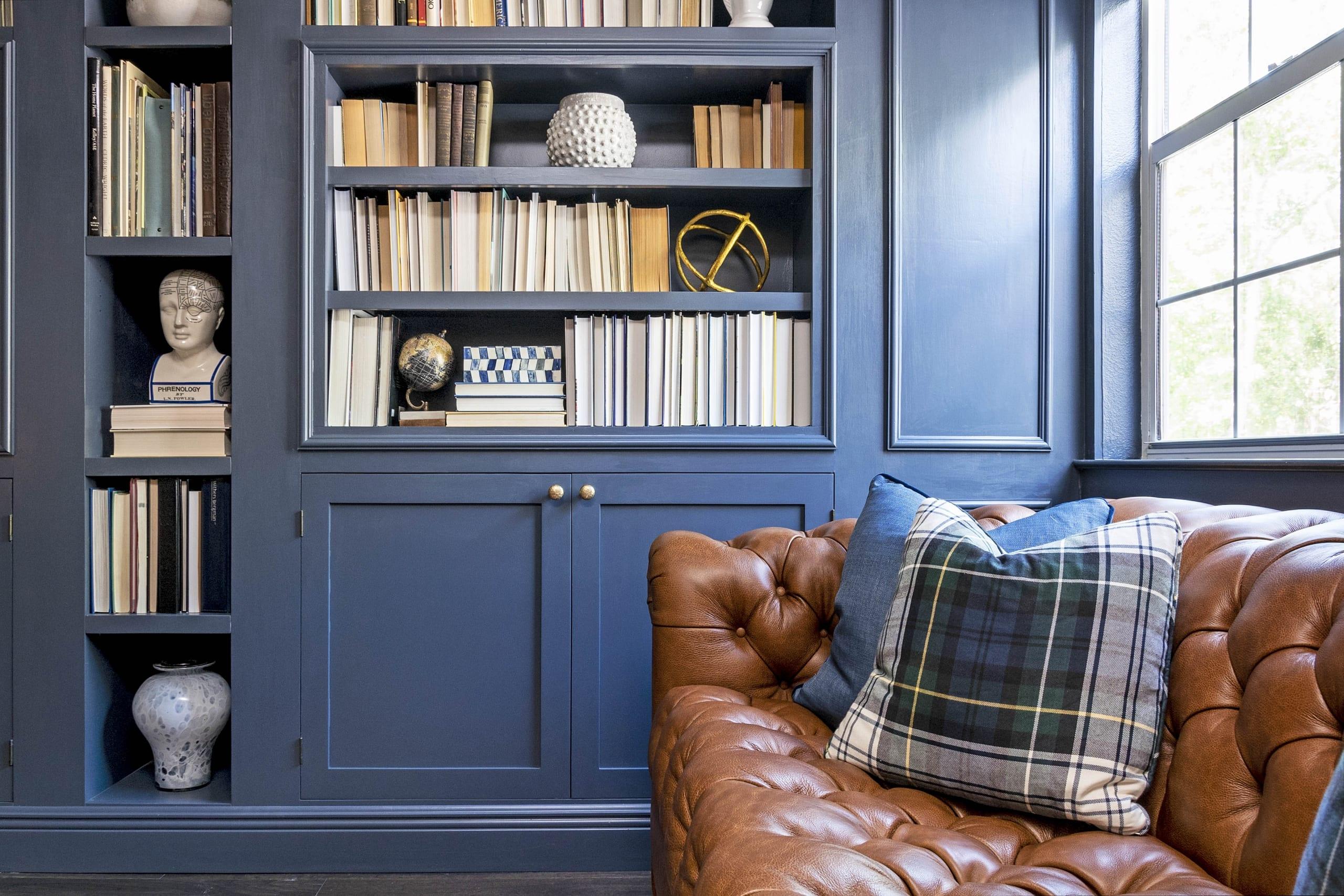Kristine Bishop Design Dark Blue Book Shelf Cabinets Brown Leather Couch Blue Cushions Tartan Pillows