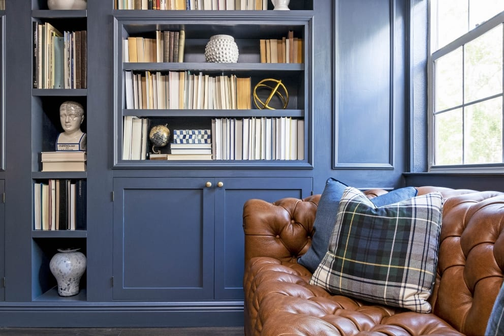 Kristine Bishop Design Dark Blue Book Shelf Cabinets Brown Leather Couch Blue Cushions Tartan Pillows