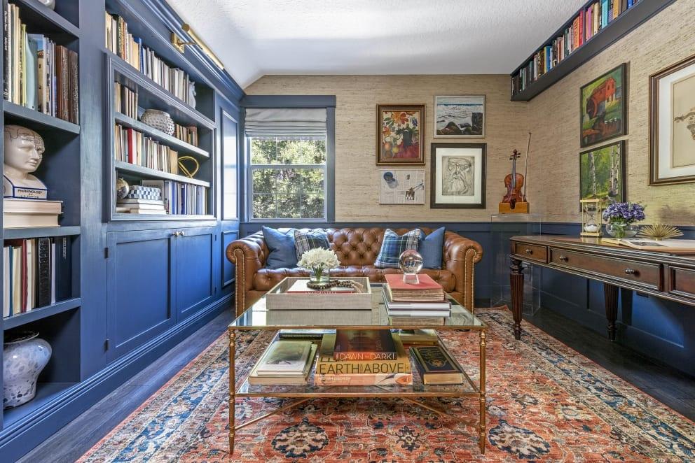 Kristine Bishop Design Dark Blue Book Shelf Cabinets Brown Leather Couch Tartan Pillows Dark Rose Wood Study Desk Persian Rug Clear Perspex Plinth Violin Glass Coffee Table