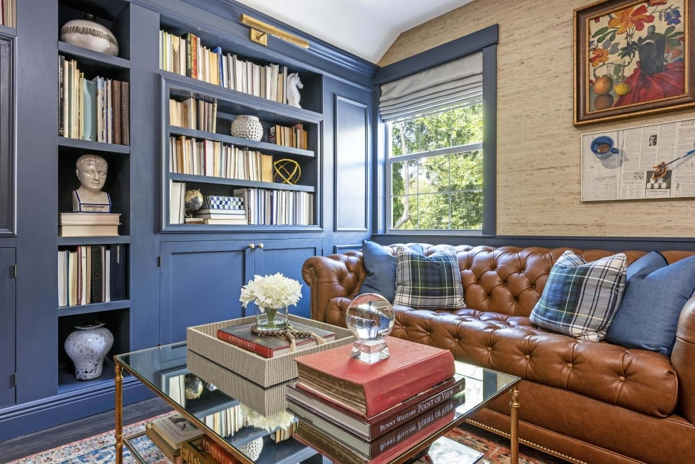 Kristine Bishop Design Dark Blue Book Shelf Cabinets Brown Leather Couch Tartan Pillows Red Persian Rug Glass Coffee Table Textured Biege Wall Paper