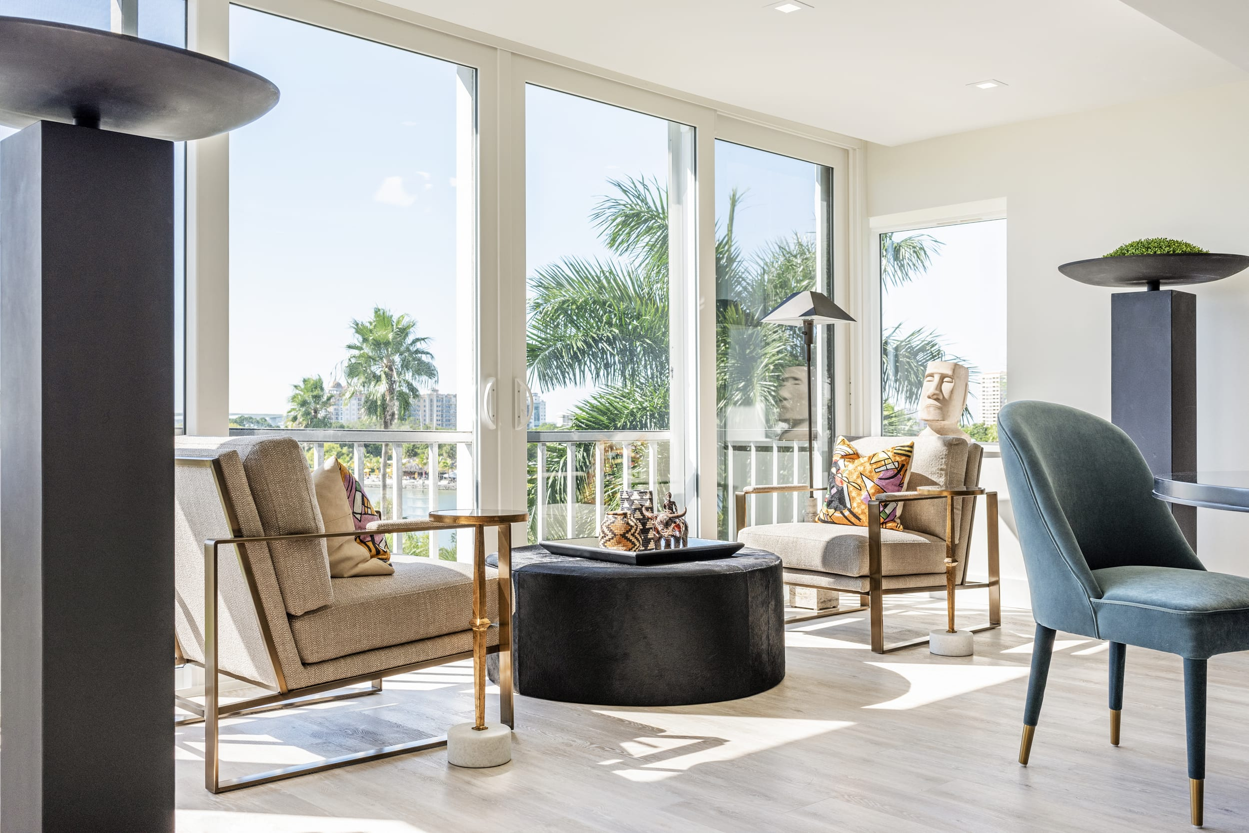 Coast View Gold Frame Arm Chairs Black Suade Pouffe Blonde Wood Floors