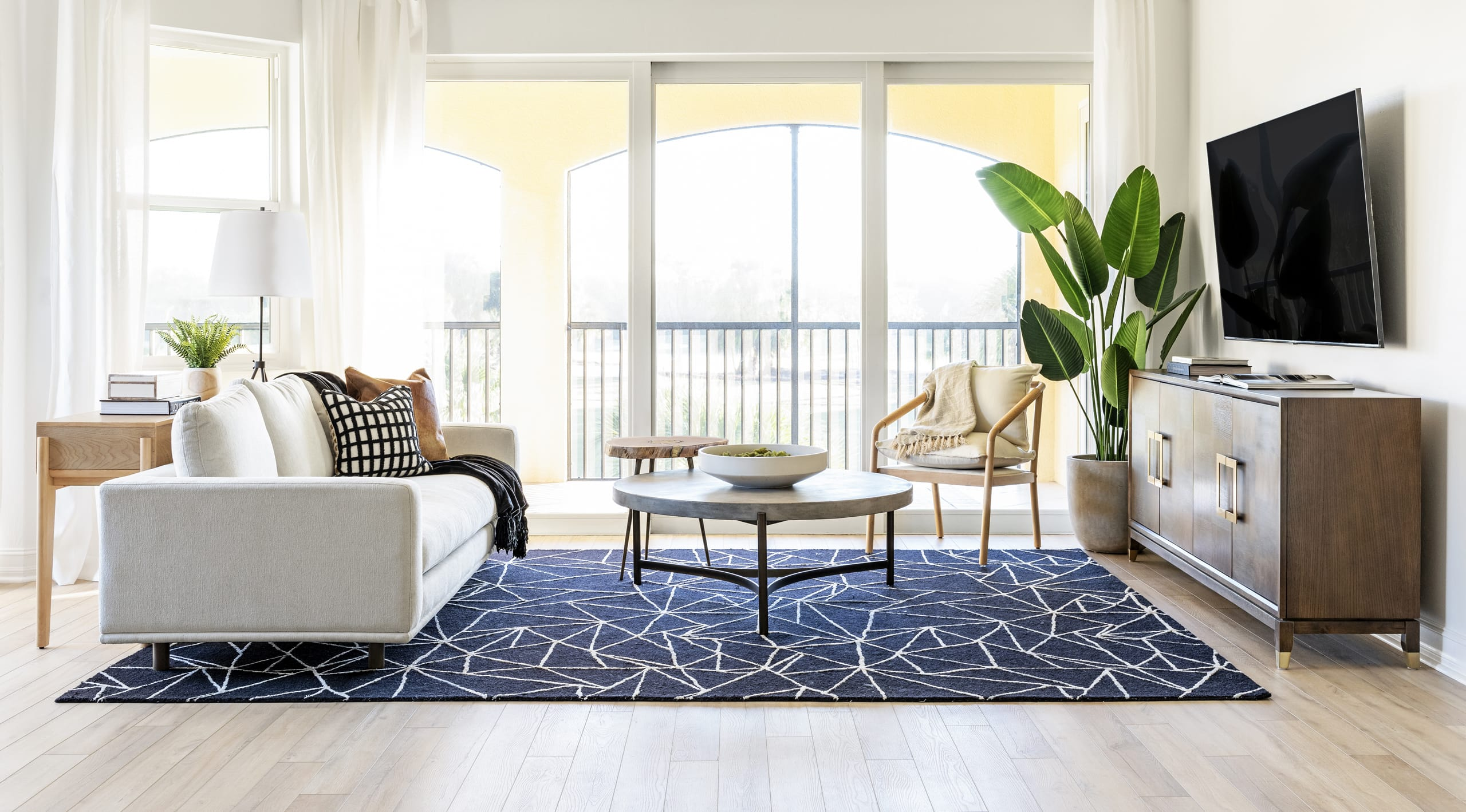 Contemporary Living Room Dark Blue Pattern Rug Stone Coffee Table White Couch Organic Colours