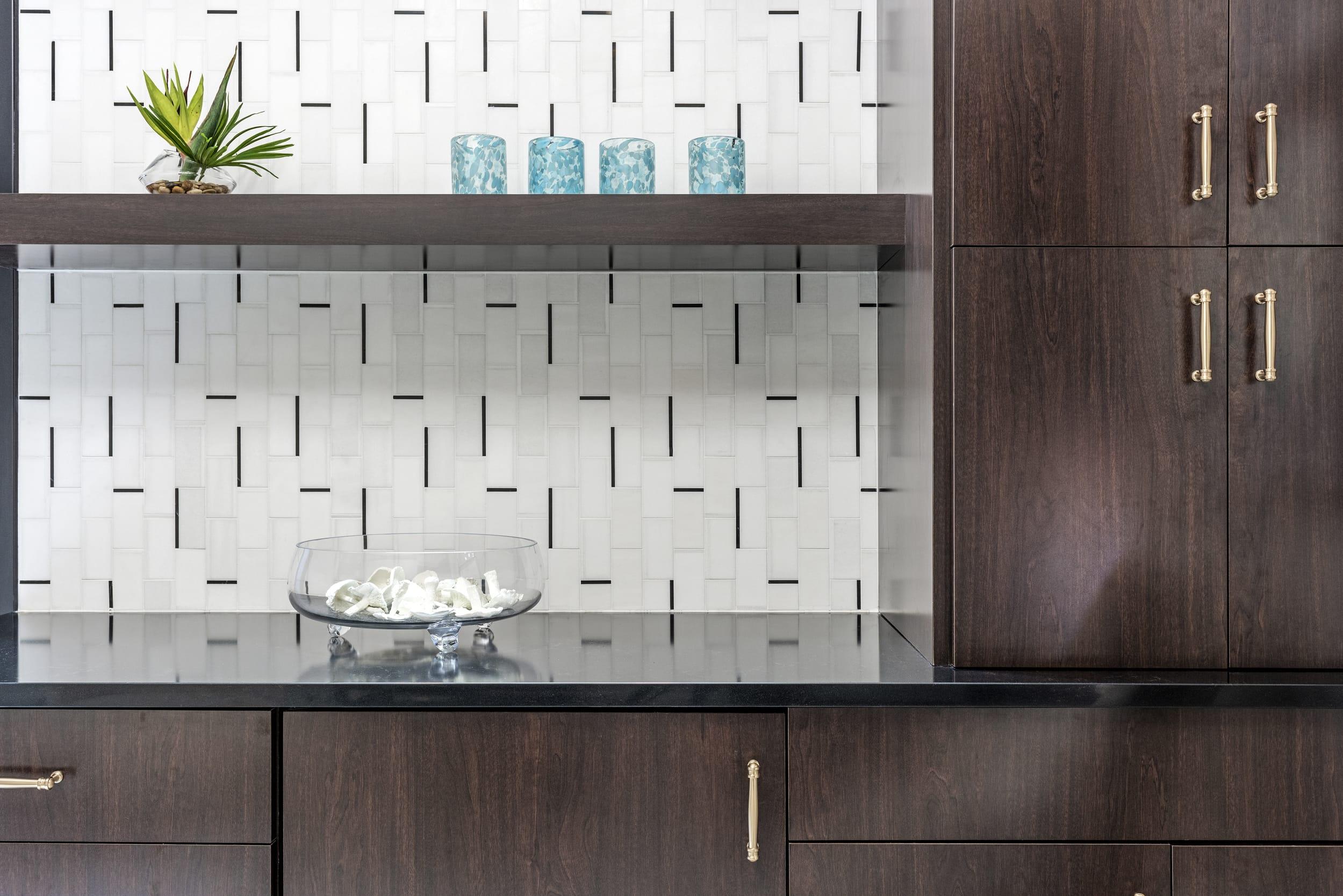 Hazelnut Cabinets Brass Handles White Tile With Linear Black Line Pattern Blue Spec Glasses